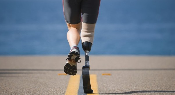 An athlete with a prosthetic leg running down the road towards the ocean.
