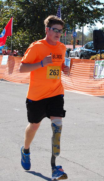DJ competes in a 5K wearing his prosthesis from Amputee Blade Runners.